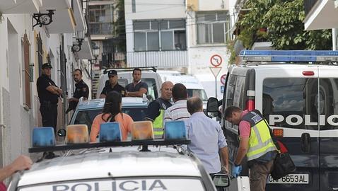 Agentes vigilan la puerta de la vivienda donde se hallaron los cadáveres