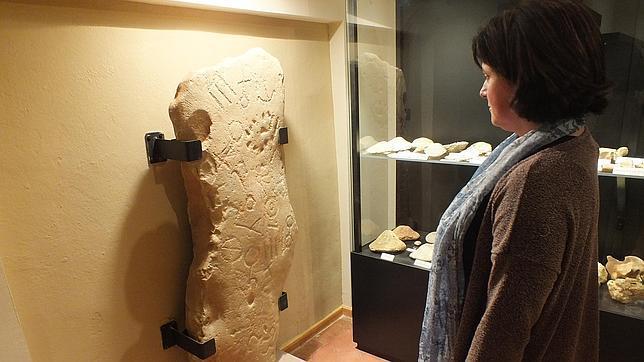 Una mujer contempla la estela ubicada en el Museo Arqueológico de Montoro