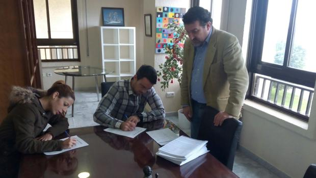 Dos jóvenes estampan sus firmas, en presencia del abogado Manuel Martos, promotor de la iniciativa