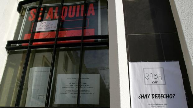 Un cartel de alquiler junto a otro que se queja del precio de los mismos en Córdoba