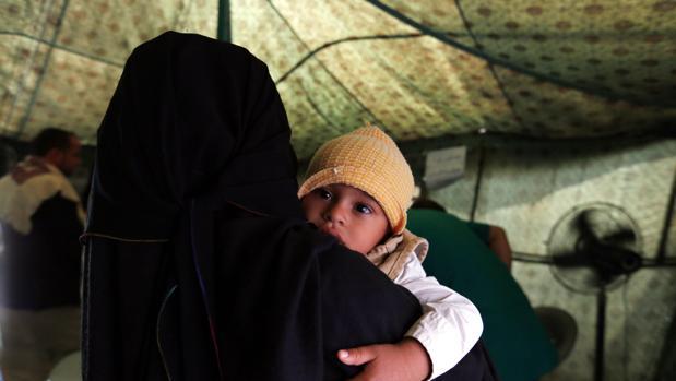 Una madre sostiene a su hijo enfermo de cólera en un hospital de campaña en Yemen