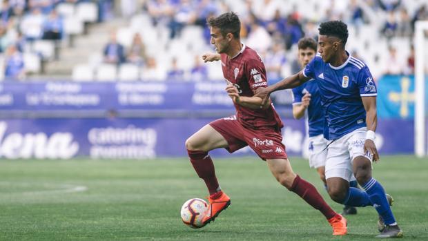 Álex Carbonell conduce el balón perseguido por Yoel Bárcenas en el Real Oviedo-Córdoba CF