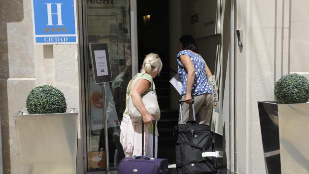 Una pareja de turistas acceden a un hotel de Málaga capital.
