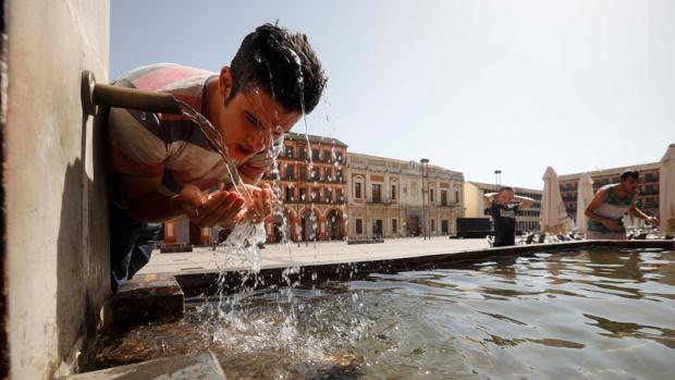 Un joven se refresca en una fuente