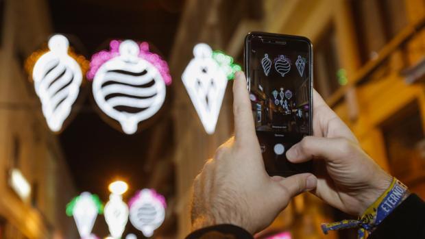 Un hombre fotografía el alumbrado navideño de una calle comercial de Córdoba