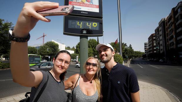 Un selfie de unos turistas frente a un termómetro de la calle en Córdoba