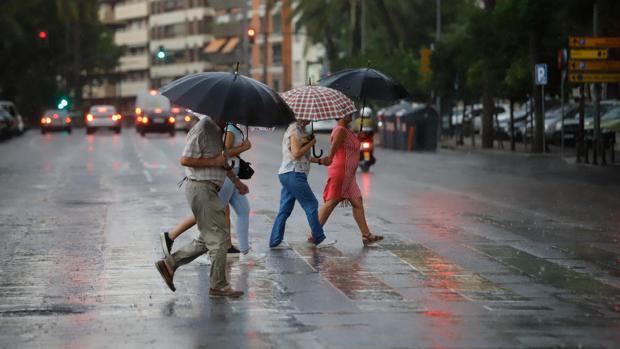 Un grupo de personas huye de la lluvia en el centro de Córdoba