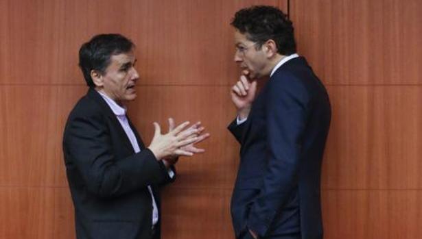 El ministro griego Tsakalotos conversa con el presidente del Eurogrupo, Disselbloem, en un receso de una reunión del Ecofin en Bruselas