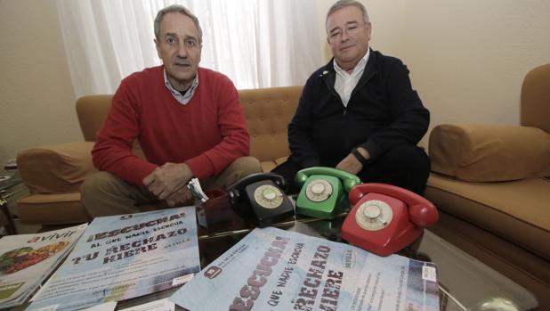 Manuel García Carretero, presidente del «teléfono de la esperanza» en Sevilla, junto a Antonio, voluntario, y los telefónos rojo, negro y verde con los que se empezó la actividad hace casi medio siglo