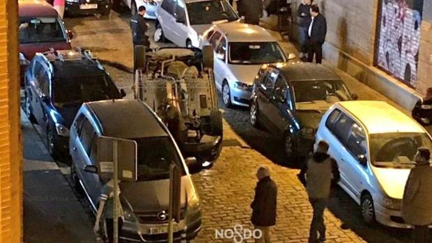 Momento en el que los servicios de emergencias acuden para auxiliar a los ocupantes del coche volcado en Sevilla