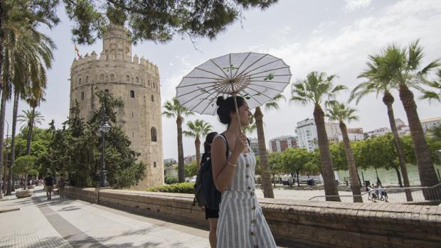 Una mujer se protege del sol a los pies de la Torre del Oro