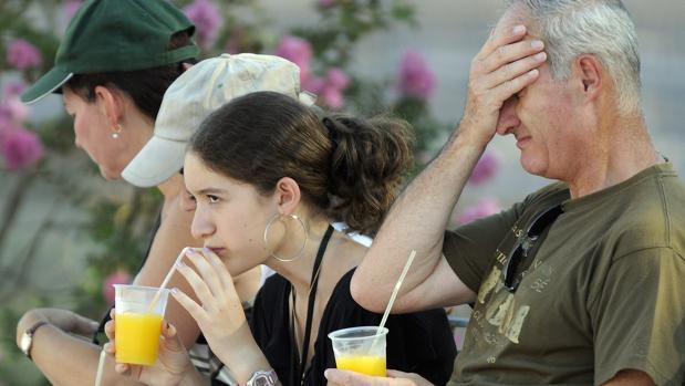 Turistas en la Plaza de España refrescándose con una bebida fría